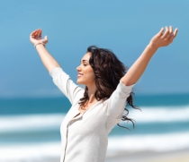 joyous-woman-on-beach-arms-raised