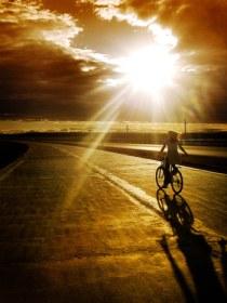 woman-riding-bike-highway-sun