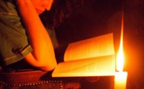 person-reading-book-by-candlelight