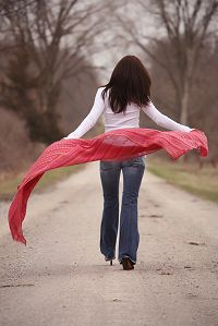 woman-walking-down-road-billowing-red-shawl