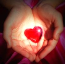 two-hands-holding-a-glowing-heart