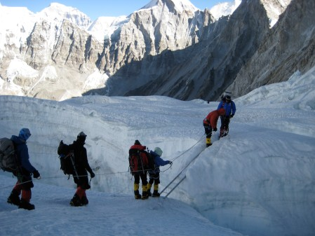 lori-schneider-in-green-hood-crossing-a-crevasse-on-everest