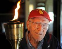 Louis Zamperini, 94, at his Hollywood home. The flame still burns in him as he holds the olympic torch he carried at the 1984 Olympic Games. (Brad Graverson )