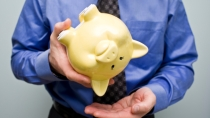 man-holding-empty-piggy-bank