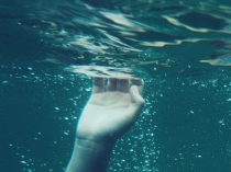 hand-reaching-up-ocean-water